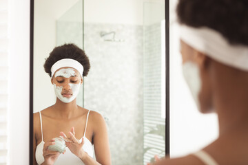 Woman applying face mask while looking in the mirror