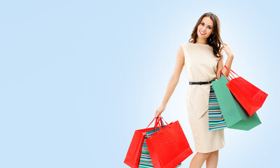 Happy smiling beautiful woman holding red shopping bags, standing against light blue color background, with copy space for some slogan or text. Consumers and sales concept picture.