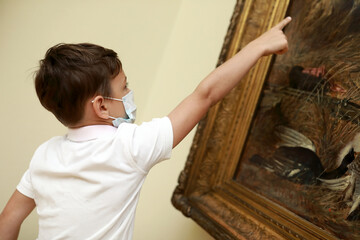 Boy wearing protection mask in picture gallery