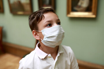 Child wearing medical protection mask in art gallery