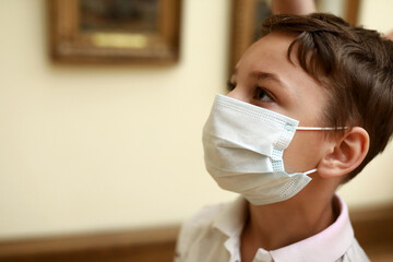 Kid wearing protection mask in picture gallery