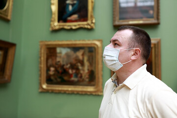 Man wearing protection mask in picture gallery