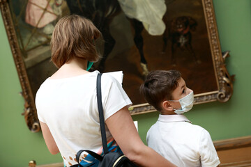 Mother and son wearing protection mask in museum
