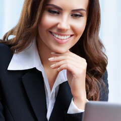 Portrait image of happy smiling young businesswoman in black confident style suit using laptop computer at office. Success in business, job and education concept. Square.