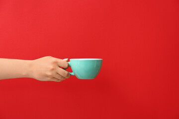 Papiers peints Cafe Hand with cup of hot coffee on color background