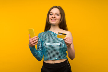 Lady buying online with a credit card and smart phone on yellow background