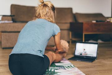 Fototapeta Woman Doing Exercises At Home Watching Youtube obraz