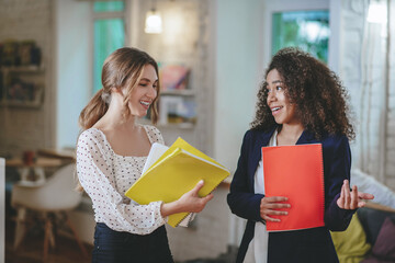 Two successful girls with documents talking well