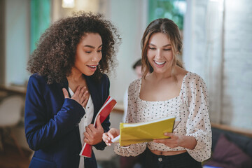 Two young girls with papers standing joyfully chatting