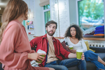 Boyfriend and girlfriend with coffee looking at girlfriend sitting back