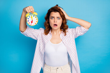 Portrait of her she nice attractive lovely puzzled worried wavy-haired girl holding in hand wake-up clock late first lecture isolated on bright vivid shine vibrant blue color background