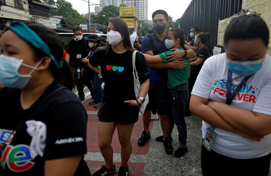 ABS-CBN employees react after the Philippine congress voted against the renewal of the broadcast network's 25-year franchise, outside ABS-CBN headquarters, in Quezon City