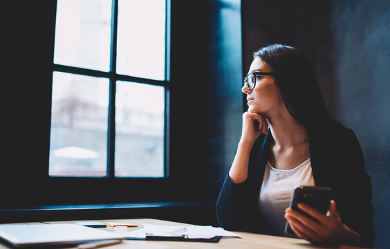 Portrait of mindful young formal dressed female owner working with financial documents and reports waiting for feedback from bank confirming credit thinking over economic strategy using wifi in office
