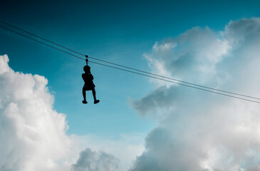 Low Angle View Of Man Hanging On Zip Line Against Sky