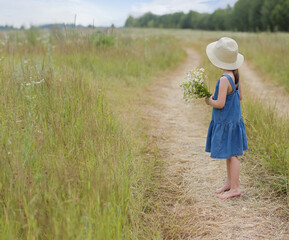 Photo sur Plexiglas Doux monstres Little girl with bouquet of chamomiles looks away towards the horizon