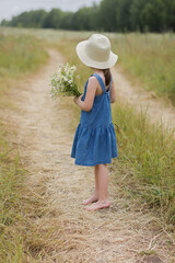 6 years old girl with bouquet of chamomiles looks away towards the horizon