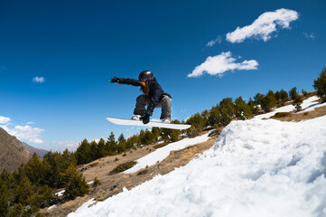 Stylish young girl snowboarder does the trick in jumping from a snow kicker against the blue sky clouds and mountains in the spring.