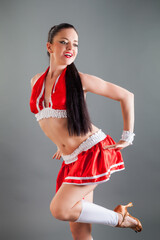 closeup young active brunette woman in red cheerleader costume poses for photo