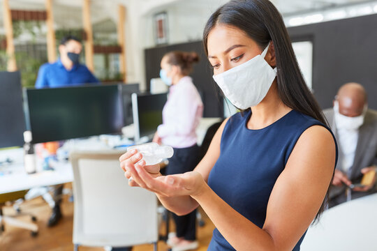 Woman using face mask in office while disinfecting hands