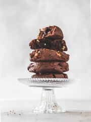 Close-up Of Stack Of Chocolate Chip Cookies On Crystal Glass Stand On Table