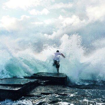 Waves Crashing At Rocks And Man