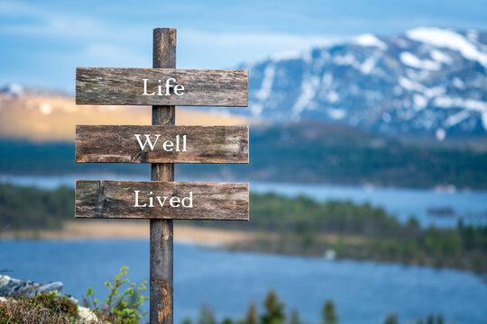 life well lived quote/text on wooden signpost outdoors in landscape scenery during blue hour and sunset.