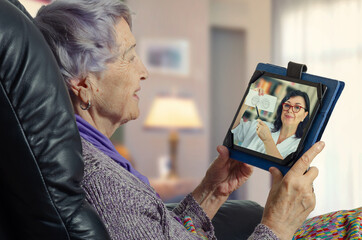 Elderly woman carefully looks at the telemedicine ophthalmologist on the screen of her tablet. She enjoys a remote appointment with the doctor.