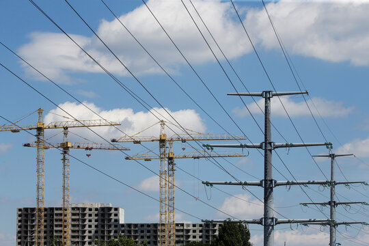 Building cranes and power lines connecting pylons of high-tension electricity are seen in Kyiv