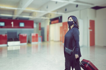 Middle-aged woman in a black protective mask walks through an empty passenger registration hall in an airport.