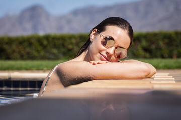 Portrait of woman with sunglasses in the pool