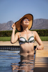 Woman with hat and sunglasses in the pool