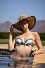 Portrait of woman with hat and sunglasses in the pool