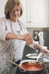 Woman Preparing Food In Kitchen At Home - fototapety na wymiar