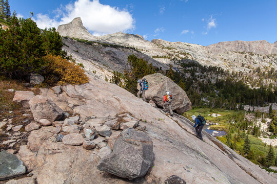 Three male backpackers ascend a steep rock face on the northeast side of Douglas Peak in the Wind River Mountain Range in Wyoming. In the distance, the peak name 'The Fortress' is seen.