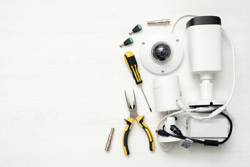 Modern white security cameras and work tools on the table background. Video surveillance concept background.