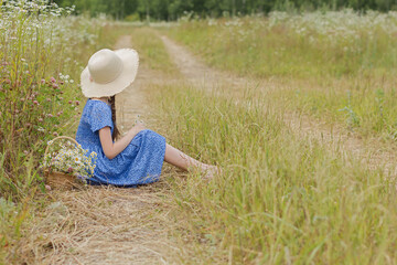 10 years old girl in the blue dress and basket of flowers on the rural field