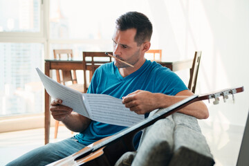 Mid Adult Man Reading Acoustic Guitar Sheet Music In Apartment
