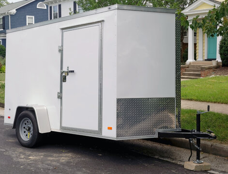 White utility trailer front and side view parked on residential neighborhood street.