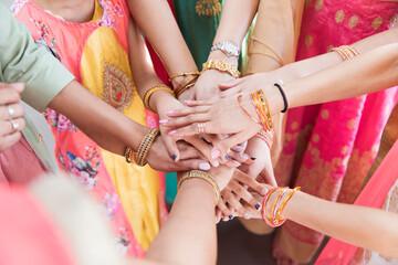 Indian women in bracelets joining hands in huddle