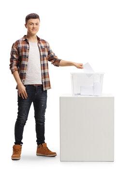 Young man putting a vote in an election box and looking at the camera
