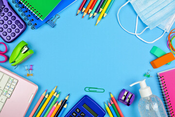 School supplies and COVID 19 prevention items. Frame on a blue paper background. Back to school during pandemic concept.