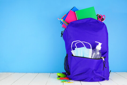 Backpack full of school supplies and COVID 19 prevention supplies. Blue background. Back to school during pandemic concept.