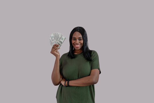 African American girl holding lot of money banknotes and smiling