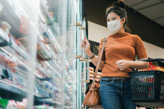 new normal after covid epidemic young smart asian female shopping new lifestyle in supermarket with face shild or mask protection hand choose fresh vegetable of fruit new normal lifestyle