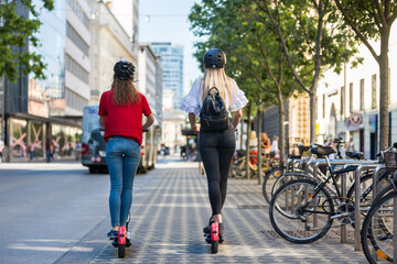 Rear view of trendy fashinable teenager girls riding public rental electric scooters in urban city environment. New eco-friendly modern public city transport in Ljubljana, Slovenia.
