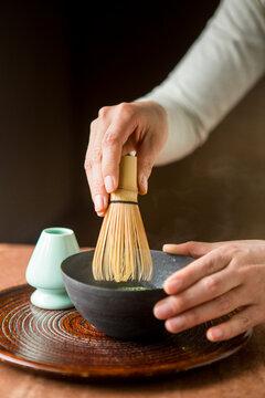 Woman making matcha tea traditional Japanese style.