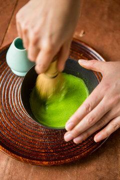 Woman stirring green matcha tea traditional Japanese style.