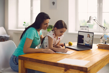 Online school. Family mom and litle girl does a lesson listens to the teacher using a laptop video chat conference remotely sitting at home.