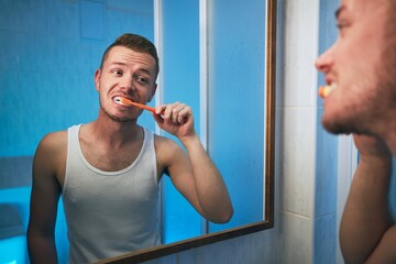Man brushing teeth in home bathroom