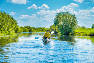People on kayak trip on blue river landscape and green forest with trees blue water clouds sky